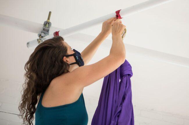 Lora hanging up an aerial yoga silk